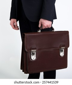 Portrait of successful business man with bag in grey background and space for text, Closeup Of Businessman Holding Briefcase Going To Work, man walking with bag,Business man hands with briefcase