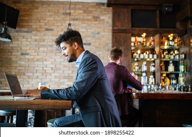 Portrait of a successful business man sitting at the cafe working on a laptop.