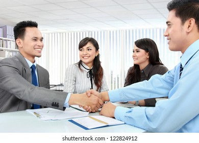 Portrait of successful business team shaking hands with eachother in the office