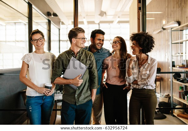Portrait of successful business team standing together and smiling. Multi ethnic business people at startup.