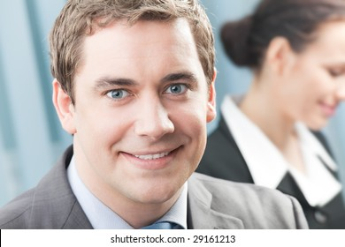 Portrait of successful businessman and colleague on background, at office