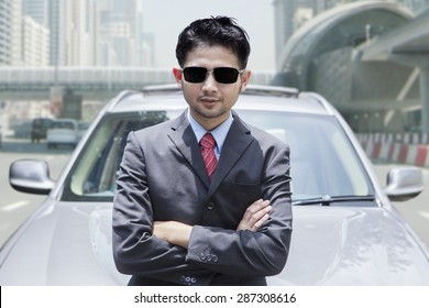 Portrait of successful businessman cross hands while standing in front new car on the road