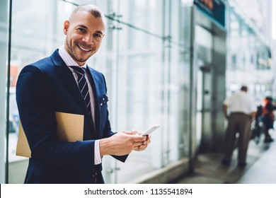 Portrait of successful businessman dressed in formal wear smiling at camera while messaging in online chat on modern smartphone.Prosperous positive proud ceo typing text notification on telephone
