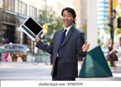 Portrait of successful businessman holding laptop and laughing