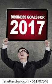 Portrait of successful businessman lifting up billboard with text of business goals for 2017 on a board