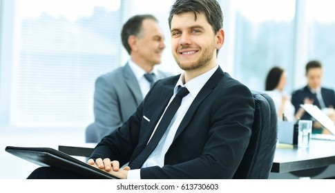 portrait of a successful businessman in the office on the background of their team