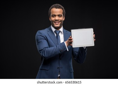 Portrait of successful businessman presenting digital tablet isolated on black