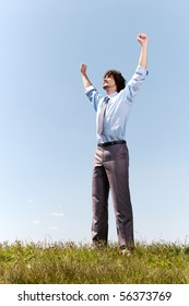 Portrait of successful businessman raising arms while standing on the grass