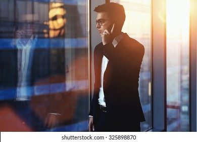 Portrait of successful businessman talking on mobile phone while standing against window in hallway of modern office interior, young confident man having cell telephone conversation during work break