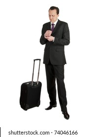 Portrait of a successful businessman with travel bag awaiting his flight. Studio shot, isolated on white background
