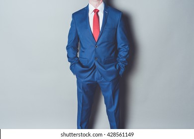 Portrait of successful businessman wearing dark blue suit and red tie against gray background