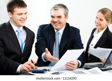 Portrait of a successful businessteam sitting at the table with documents and working with them