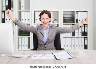 Portrait of successful businesswoman with arms outstretched sitting at desk in office