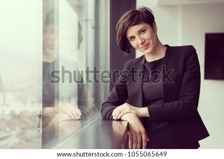 Portrait Of Successful Businesswoman by the window Entrepreneur At Busy startup Office