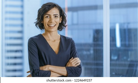 Portrait of the Successful Businesswoman Crossing Her Arms and Smiles. Beautiful Woman Executive Standing in Her Office.