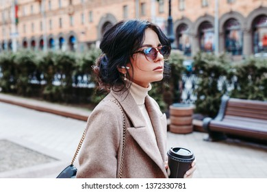 Portrait of successful businesswoman holding cup of coffee In hand on her way to work