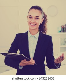 Portrait successful businesswoman holding documents in hands in office