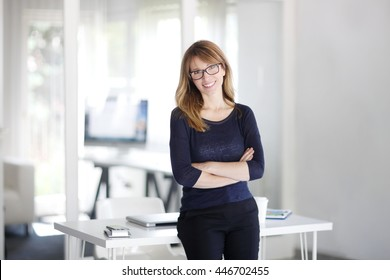 Portrait of successful businesswoman standing with arms crossed at the office. Mature professional woman looking at camera and smiling.
