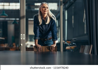 Portrait of successful businesswoman standing leaning to a chair in meeting room and looking away. Senior female entrepreneur in conference room.