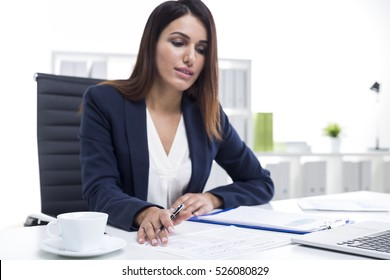 Portrait of a successful businesswoman in a suit working at her white table in office. She is reading documents and taking notes.