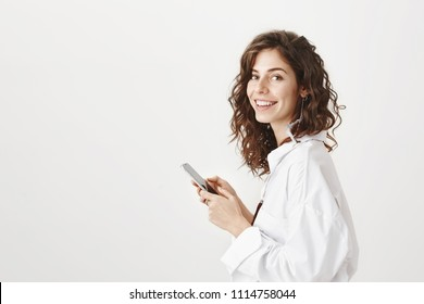 Portrait of successful caucasian businesswoman standing in profile, holding smartphone and smiling at camera, expressing positive emotions over gray background. Bloger shares thoughts with audience