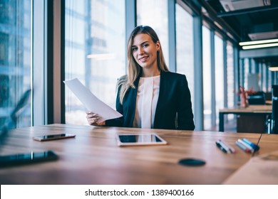 Portrait of successful caucasian female entrepreneur sitting at desktop with paper documents and looking at camera while working on strategy for good organisation of business event with partners
