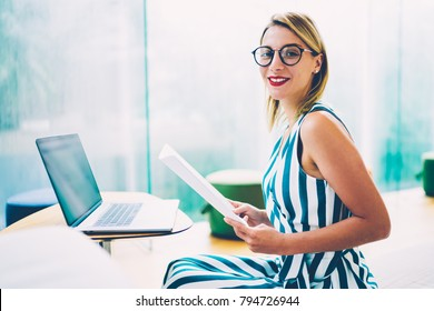 Portrait of successful cheerful businesswoman with paper documents working on organisation and creating new startup project sitting with computer in office.Young female economist posing for the camera