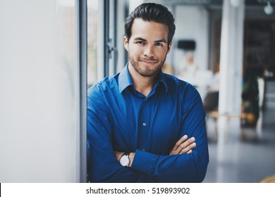 Portrait of successful confident hispanic businessman smiling and standing close from the window in modern office.Horizontal,blurred background
