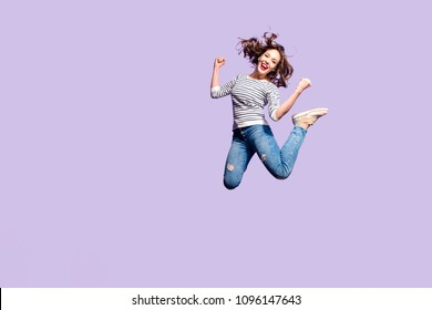 Portrait of successful crazy girl celebrating victory jumping in the air with raised fists yelling isolated on violet background, full of energy people in action concept