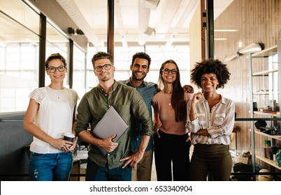 Portrait of successful creative business team looking at camera and smiling. Diverse business people standing together at startup.