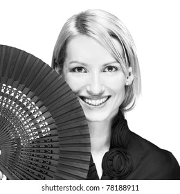 Portrait of a successful,  elegant, atractive, business woman wearing black blouse holding folding fan.