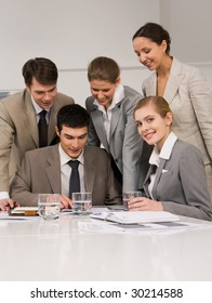 Portrait of successful employees looking at papers while confident woman smiling at camera during meeting