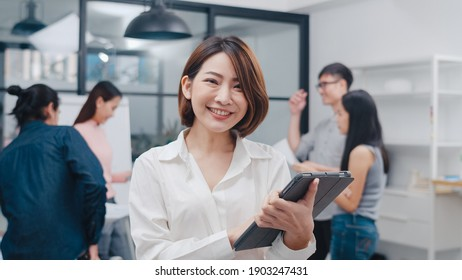 Portrait of successful executive businesswoman smart casual wear looking at camera and smile with digital table in modern office workplace. Young Asia lady standing relax in contemporary meeting room.