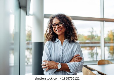 Portrait of successful female professional with her arms crossed. Smiling businesswoman standing in office.