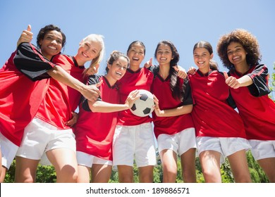 Portrait of successful female soccer players gesturing thumbs up against clear blue sky