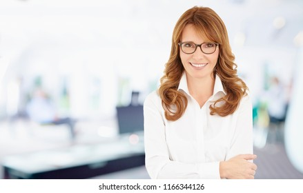 Portrait of a successful financial businesswoman standing with arms crossed in her office.