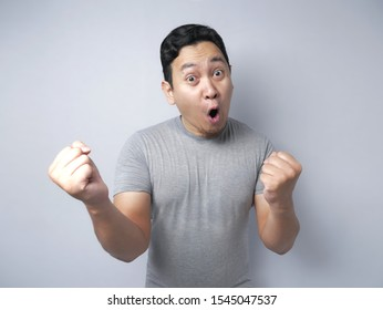 Portrait of successful funny young Asian man shows winning gesture, celebrating victory, surprised with open mouth. Hands raised above