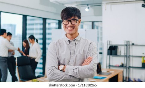 Portrait of successful handsome executive businessman smart casual wear looking at camera and smiling, arms crossed in modern office workplace. Young Asia guy standing in contemporary meeting room.