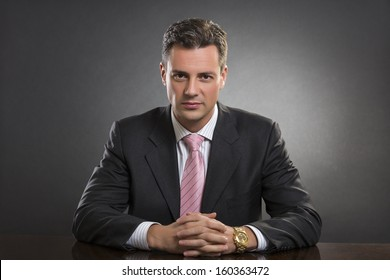 Portrait of successful handsome well-dressed young businessman looking confidently at camera in his office over dark background. Smart people.