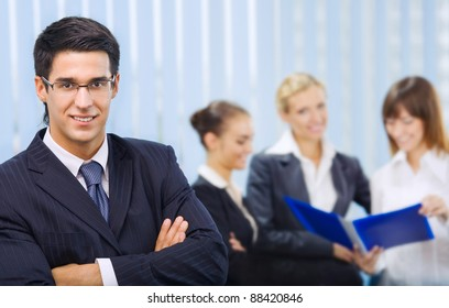 Portrait of successful happy smiling business man and business team working at office