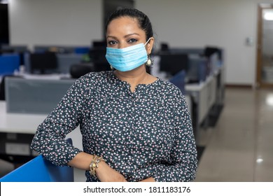 Portrait of successful Indian business woman wearing Covid protection mask and standing against office background,