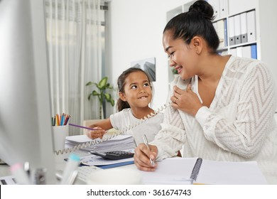 Portrait of successful Indonesian business lady and mother working in office