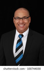 Portrait of successful intelligent businessman in dark suit and blue striped tie, wearing glasses and smiling