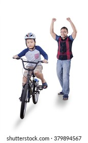 Portrait of successful little boy riding a bicycle with happy father on the back, isolated on white background