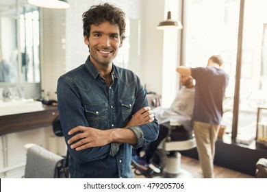 Portrait of successful male barber with crossed arms. Looking at camera