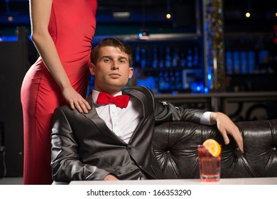 Portrait of a successful man in a nightclub, sitting on the couch, next to a woman in a red dress