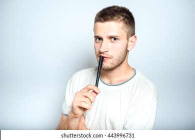 Portrait of a successful man thinking with a pen, isolated on a gray background