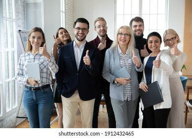 Portrait of successful mature businesswoman and team showing thumbs up Happy interns satisfied with training, giving positive feedback to senior coach, recommending good service with like gesture.