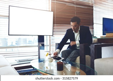 Portrait of a successful men entrepreneur holding digital tablet while sitting in modern coffee shop near empty blank screen with copy space area,elegant men preparing for the briefing using touch pad