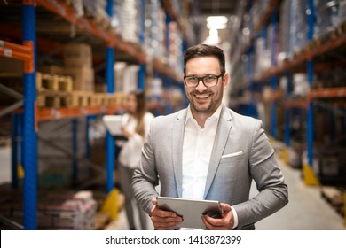 Portrait of successful middle aged caucasian manager businessman holding tablet computer in large warehouse organizing distribution. Business people.